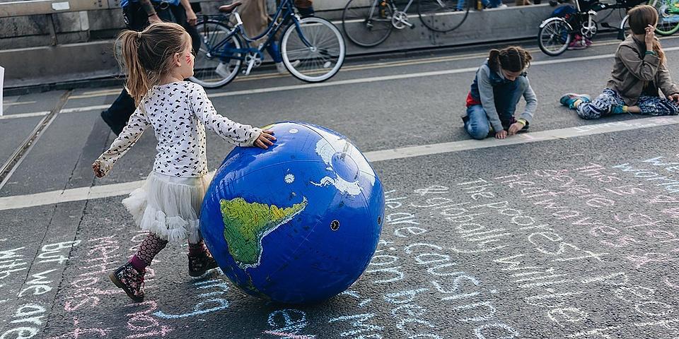 Mädchen spaziert mit Erdkugel-Ball über mit Farbkreiden beschriebene Straße
