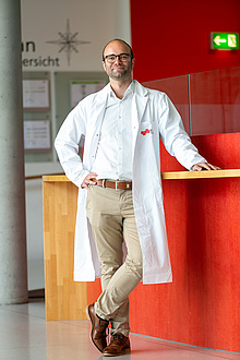 Smiling man with glasses and lab coat.