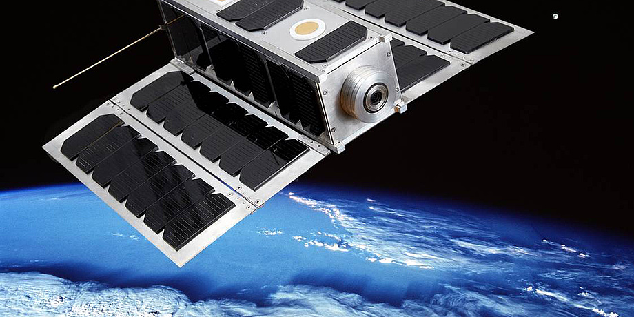 Photomontage of the nanosatellite OPS-SAT in space near the blue planet earth.