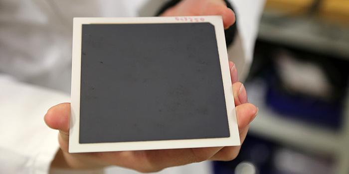 Eine Hand hält eine quadratische Platte, die mit schwarzer Masse beschichtet ist.