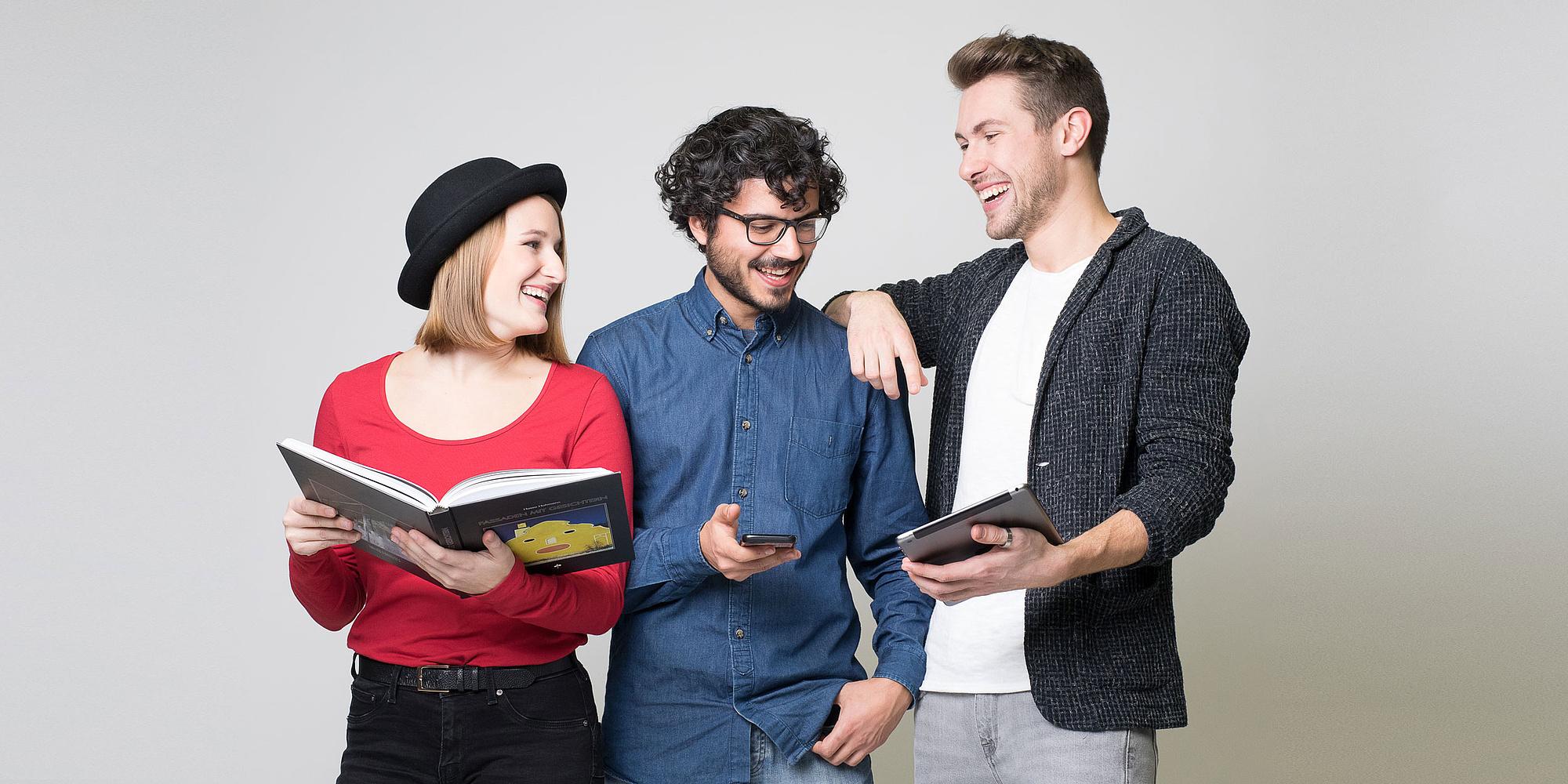 3 Studierende halten Block, Handy und iPad in der Hand und lachen.