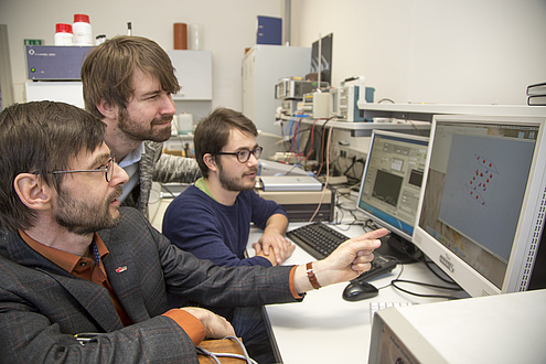 Three men sit in front of a computer monitor and analyse the research results, which are displayed on the screen in the form of a graphic.