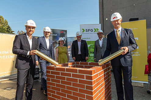 6 persons with construction helmet and foundation stone rolls in front of a small wall