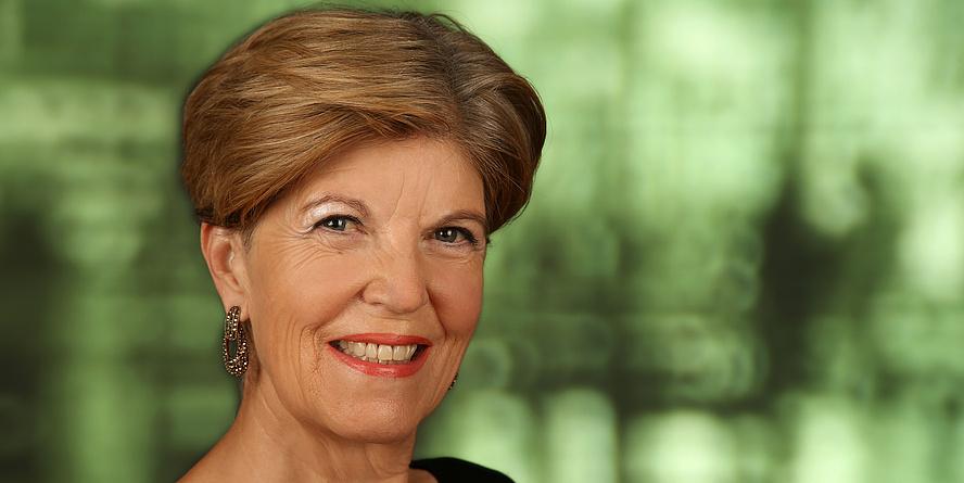 Ein Porträtfoto von Karin Schaupp vor grünem Hintergrund.