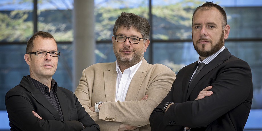Drei Männer blicken in die KAmera