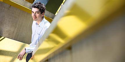 Ein Mann steht am Fuße einer gelben Treppe.