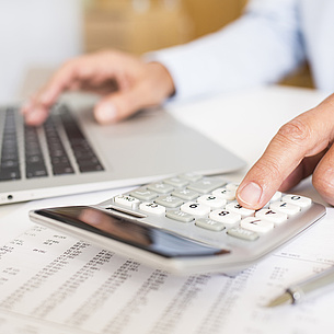 Hands operating a calculator and a laptop at the same time. Photo source: Idprod - fotolia.com