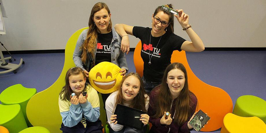 Vier Mädchen im Alter von 10 bis 14 Jahren und eine Frau mit Brille präsentieren jeweils eine Computerplatine, ein Tablet und einen drei Zentimeter großen kugelförmigen Roboter.