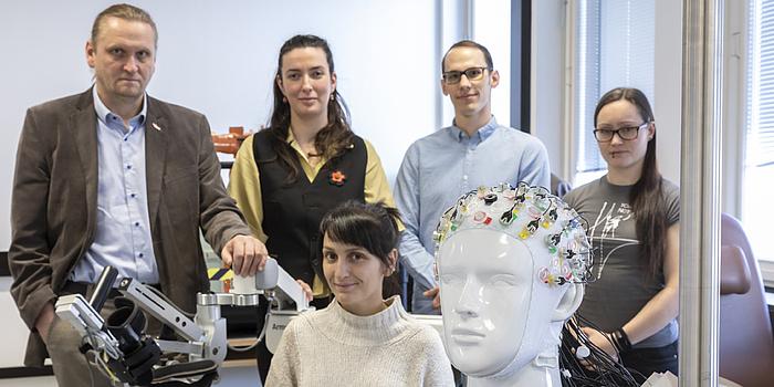 Zwei Männer und drei Frauen in einem Labor. Vor ihnen steht ein Plastik-Kopf mit mehreren bunten Elektroden.