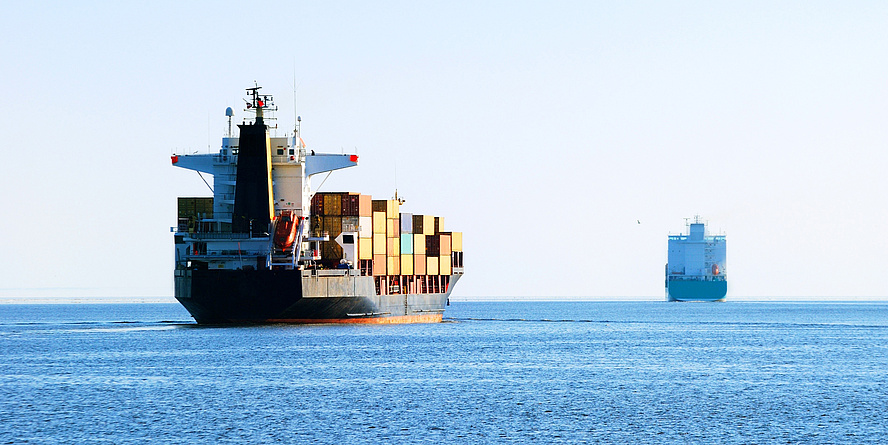 Zwei Frachtschiffe am Wasser.