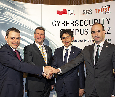 Four men in suits stand in front of the expo wall to the Cybersecurity Campus Graz and shake hands with each other.
