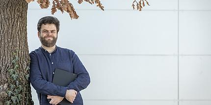 David Garcia steht an einen Baum gelehnt und hält seinen Laptop in der Hand.