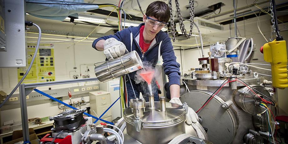 Junger Mann mit blauer Sweatjacke und Schutzbrille schüttet in einem physikalischen Labor eine Flüssigkeit durch einen roten Trichter.