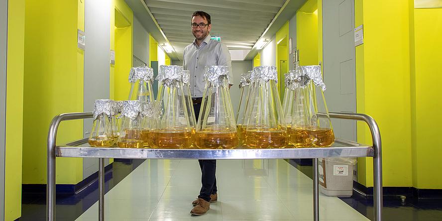 Der Forscher Gustav Oberdorfer steht in einem langen Gang mit gelben Wänden. Vor ihm steht auf einer metallenen Abstellfläche eine Reihe an Glasgefäßen.
