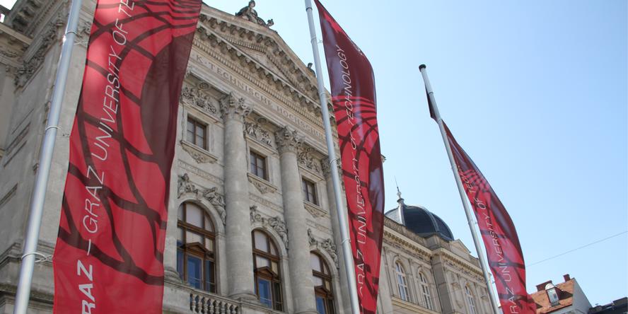 TU Graz flags and in the background the building Alte Technik of TU Graz.