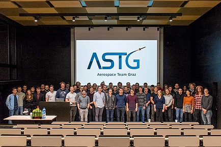 Gruppe Studierender vor einer Videowall im Hörsaal