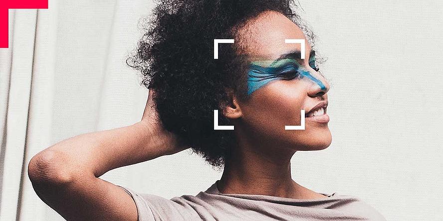 Junge Frau mit sehr auffälligem, bunten Augen-Make-up posiert in Hose-/Oberteilkombination.
