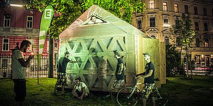 Fotomontage mit Patrick Ernst und Robert Sterzing beim arcCard shelter2.0, einer Notunterkunft aus Wellkarton, bereits aufgebaut am Campus Alte Technik.