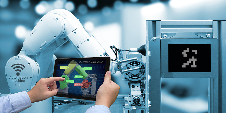 A person operates the arm of an industrial robot via a tablet.