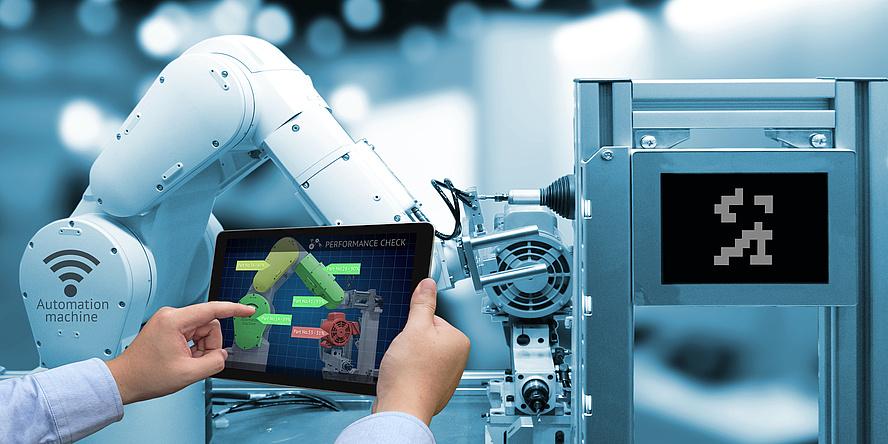 Ein Mann bedient über ein Tablet den Arm eines Industrieroboters
