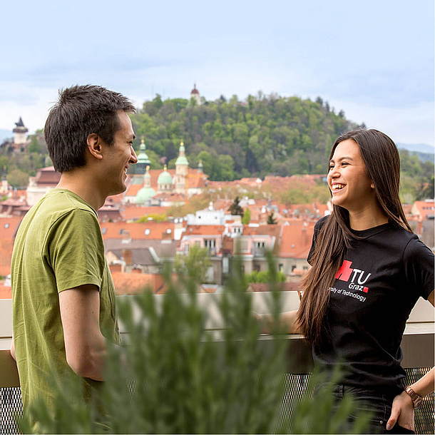 Man and woman talking on a balcony, in the background the city of Graz. Photo source: Lunghammer - TU Graz