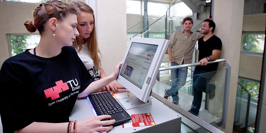 Junge Frau bei der Computereingabe, eine Kollegin blickt ihr über die Schulter.