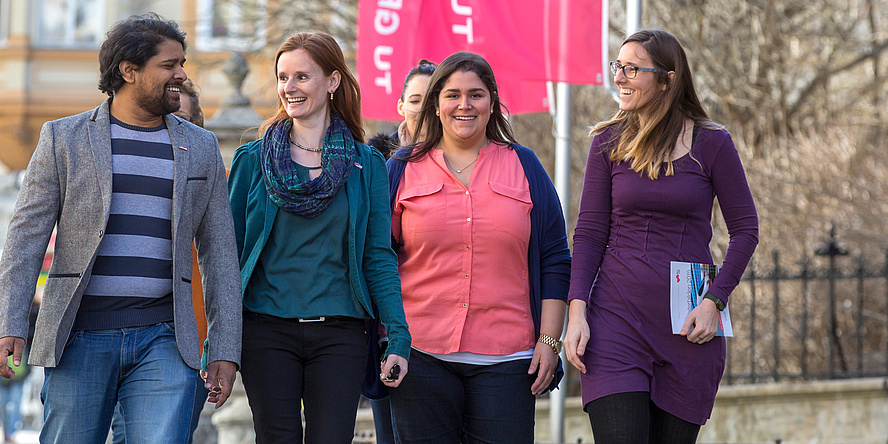 "Four staff members of different origin (three female, one male) on campus ""Alte Technik"" of TU Graz."