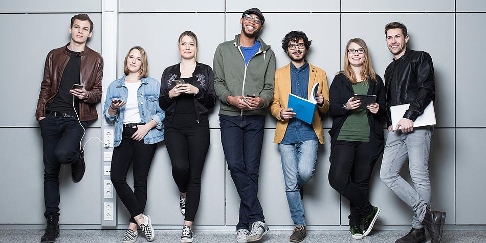 """Die """"Faces"""" der TU Graz Lukas, Benedict, Johanna, Sara, Leonardo, Verena, Lukas von links nach rechts vor einer großgefliesten Wand am Campus der TU Graz."""