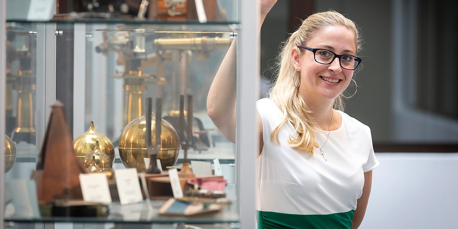 Frau mit Brille neben Metallgegenständen
