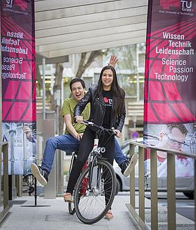 Zwei Studierende auf einem Fahrrad