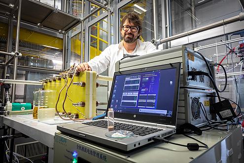 Mann mit Brille vor Bildschirm und Apparatur