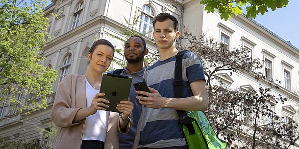 Eine junge Frau und zwei junge Männer stehen vor einem Gebäude. Sie halten ein Tablet und ein Smartphone in der Hand. Bildquelle: Lunghammer – TU Graz