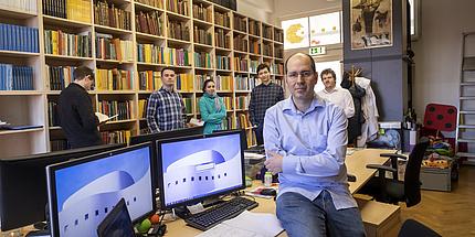 Michael Kerber sitzt auf einem Schreibtisch in einer kleinen Bibliothek. Hinter ihm steht seine Arbeitsgruppe.