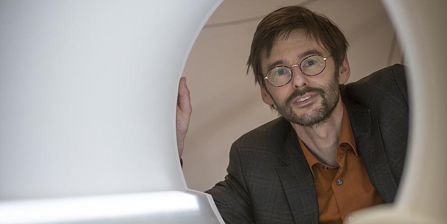 Ein Mann blickt durch eine runde Öffnung