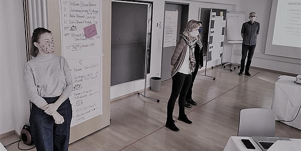 Drei Personen mit Mund-Nasen-Schutz stehen mit großem Abstand in einem Raum, im Hintergrund befinden sich Flipcharts und eine Präsentation auf einer Leinwand.