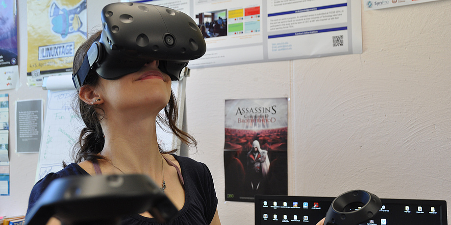 A young woman is wearing a large black VR headset.