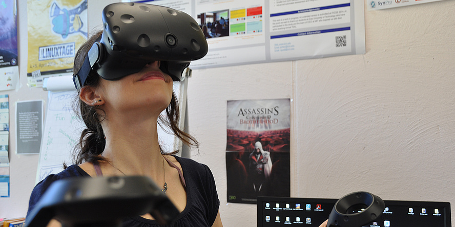 Eine junge Frau hat eine große schwarze Virtual-Reality-Brille aufgesetzt und hält in jeder Hand einen schwarzen Joystick