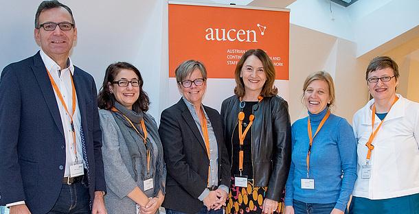 """6 Personen stehen vor einem Roll-Up mit der Aufschrift """"aucen"""". Bildquelle: AUCEN"""