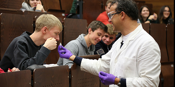 A professor wearing safety glasses and protective gloves shows a laboratory sample to students. Source: Baustädter – TU Graz