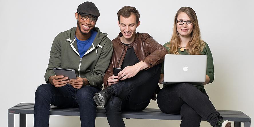 Zwei Burschen udn ein Mädchen sitzen auf einer Bank. Das Mädchen ganz rechts hat einen Laptop am Schoß.