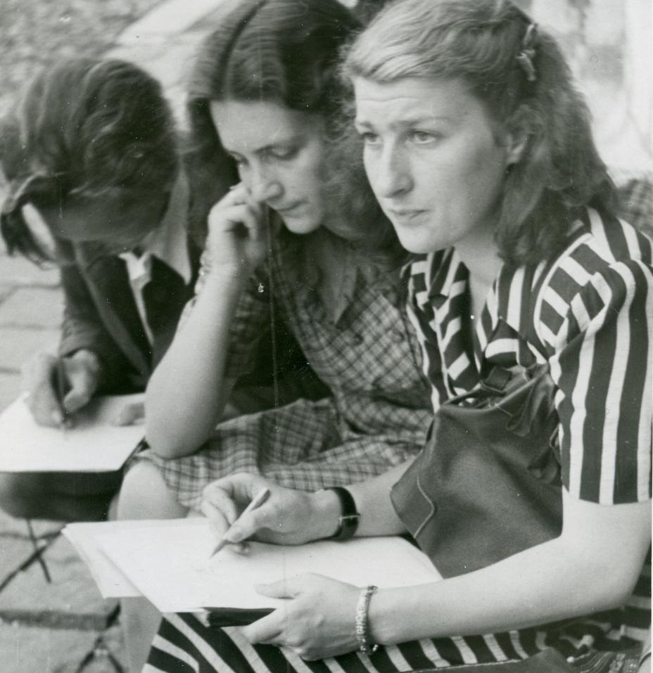 Ein junger Mann mit Anzug und Hemd mit Bleistift über ein Blatt Papier gebeugt und zwei jung Frauen mit kurzärmligen Kleidern, die rechte hält Papiere und Bleistift und blickt gerade auf. Alle drei sitzen auf Stühlen im Freien.