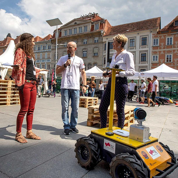 A researcher shows a robot to visitors.