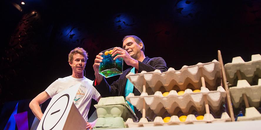 Junger Mann in weißem T-Shirt mit Headset vor dunklem Hintergrund auf einer kaum sichtbaren Bühne neben einem Mann mit dunklem Sakko und himmelblauem Shirt, der ein Miniaquarium hält. Rechts vor ihnen im Bild jede Menge Eierkartons.