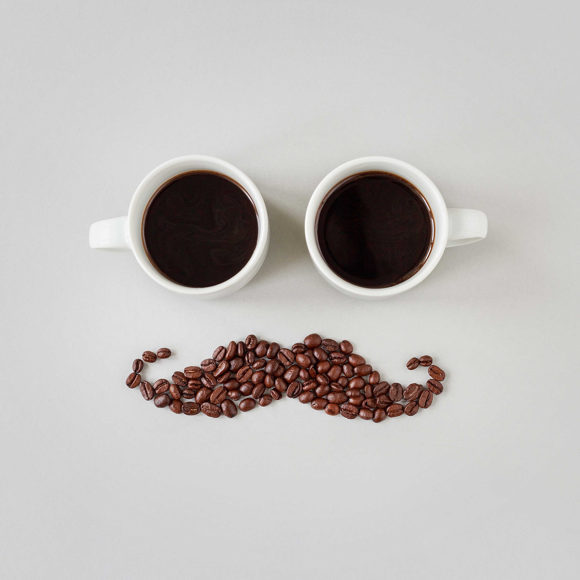 Coffee cups and coffee beans form a face with a moustache.