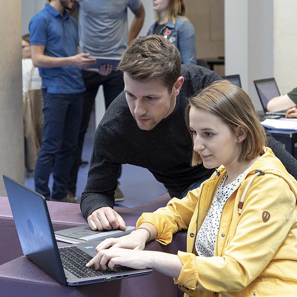 Eine junge Frau und ein junger Mann blicken in einen Laptop.