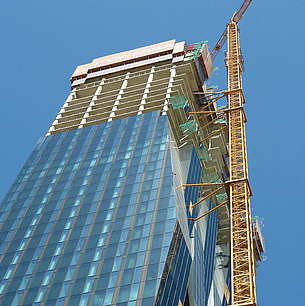 A skyscraper under construction, next to it a crane
