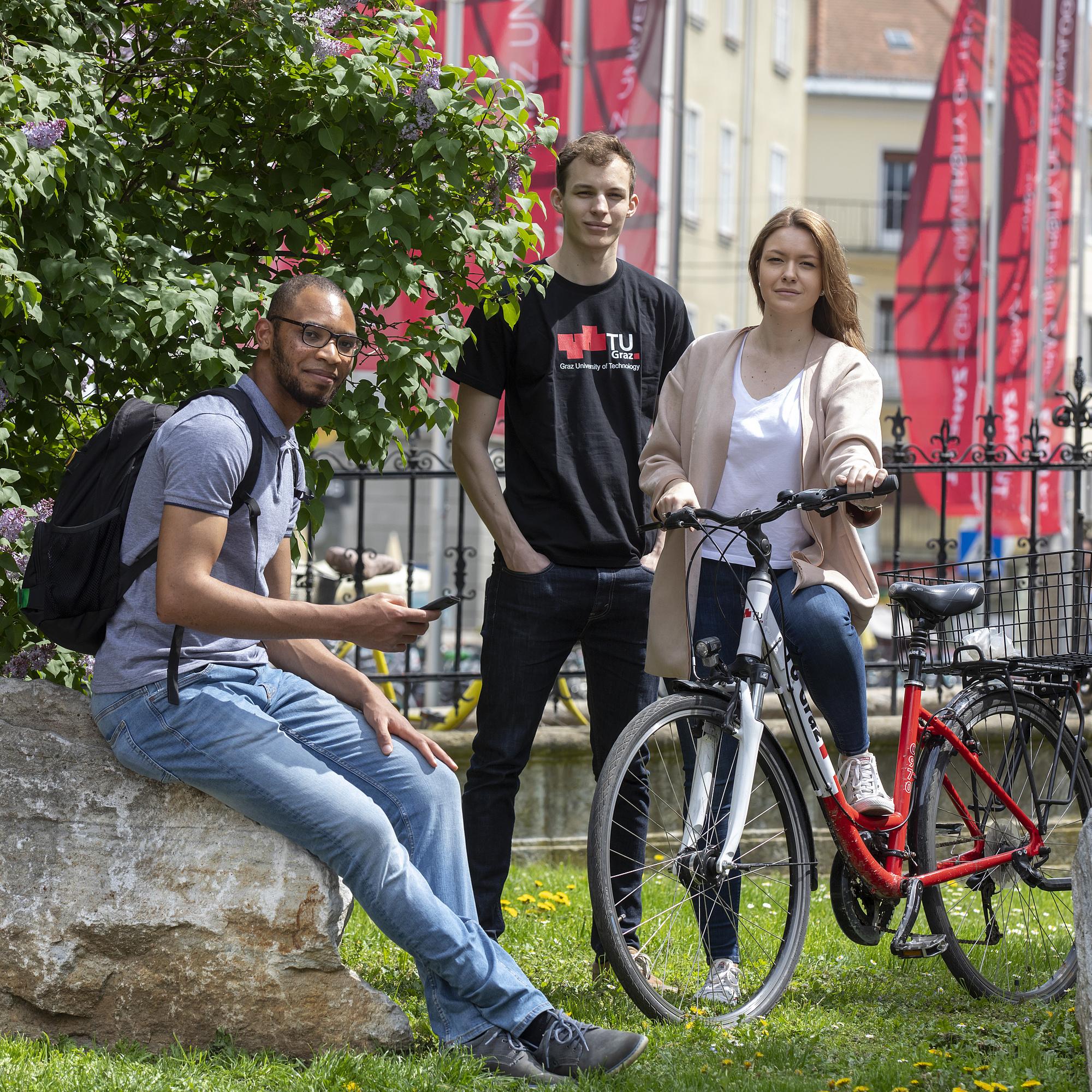 Drei junge Menschen stehen am Campus der TU Graz mit einem Fahrrad.