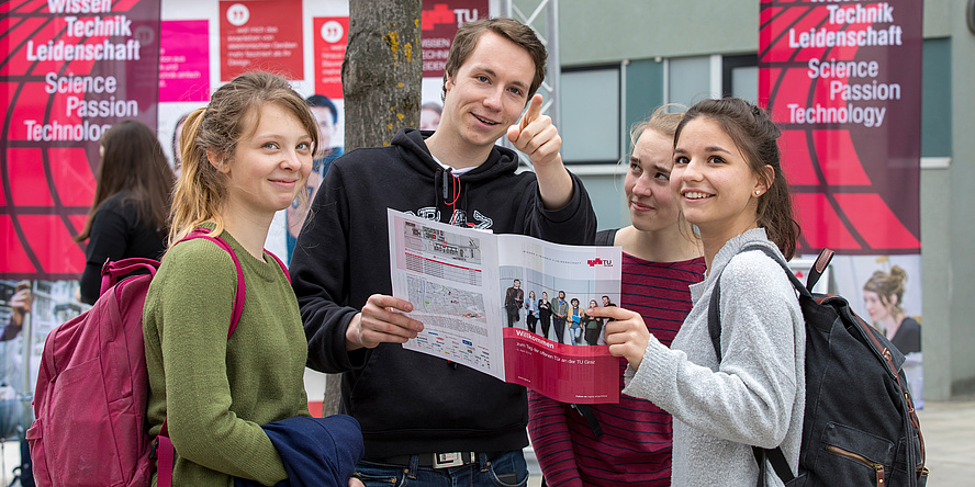 """Ein Student erklärt drei Schülerinnen etwas anhand einer Infobroschüre und richtet den Zeigefinger in Richtung Betrachterin oder Betrachter. Im Hintergrund rote Fahnen mit der Aufschrift """"Wissen, Technik, Leidenschaft""""."""