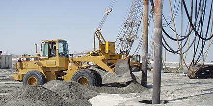 Eine große Baumaschine nimmt Bohrungen im Wüstensand vor.