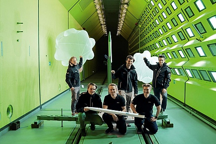 TU Graz STudierende in einem Windkanal mit Rakete und Fallschirmen in Händen